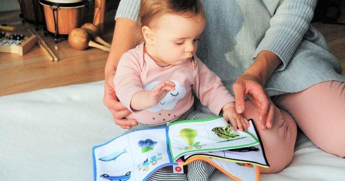 Bebê pequeno olha livro ao lado da mãe